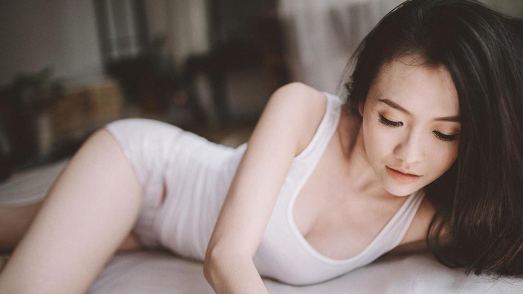 躺在床上的白色紧身吊带长发美女高清壁纸